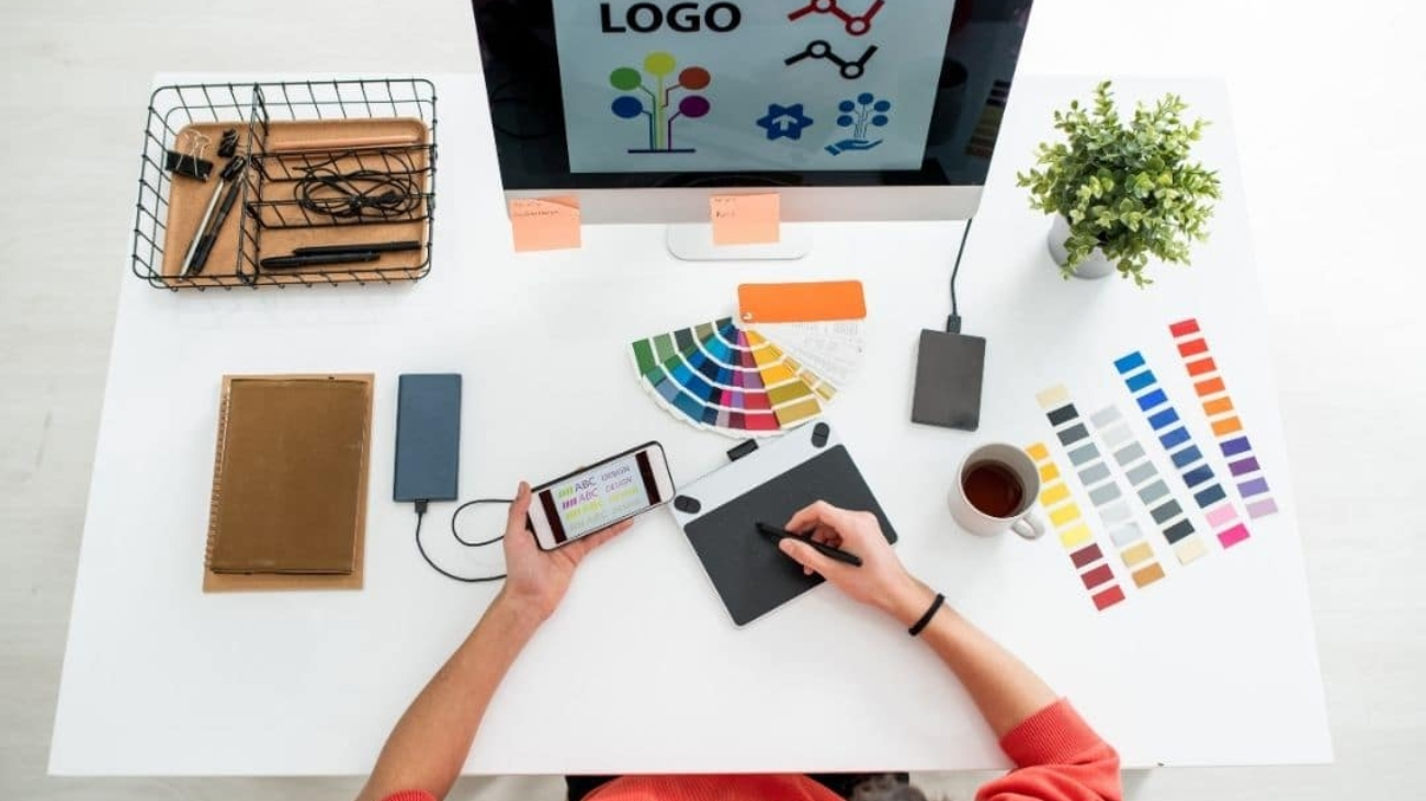 scrivania vista dall'alto con pc, color palette, cellulare e persona che disegna su pad